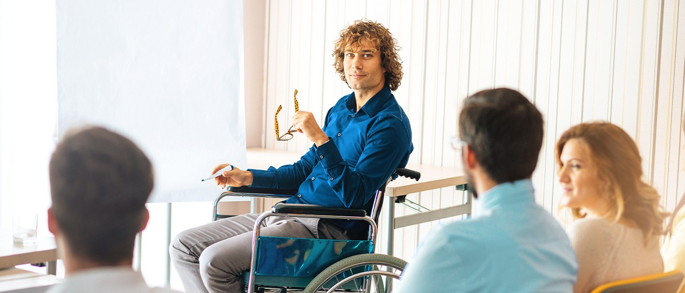 In a professional training session, a curly-haired male instructor sits in a wheelchair in front of a flipchart.