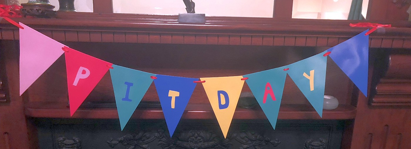 """A garland with the flags spelling """"PITDAY"""""""