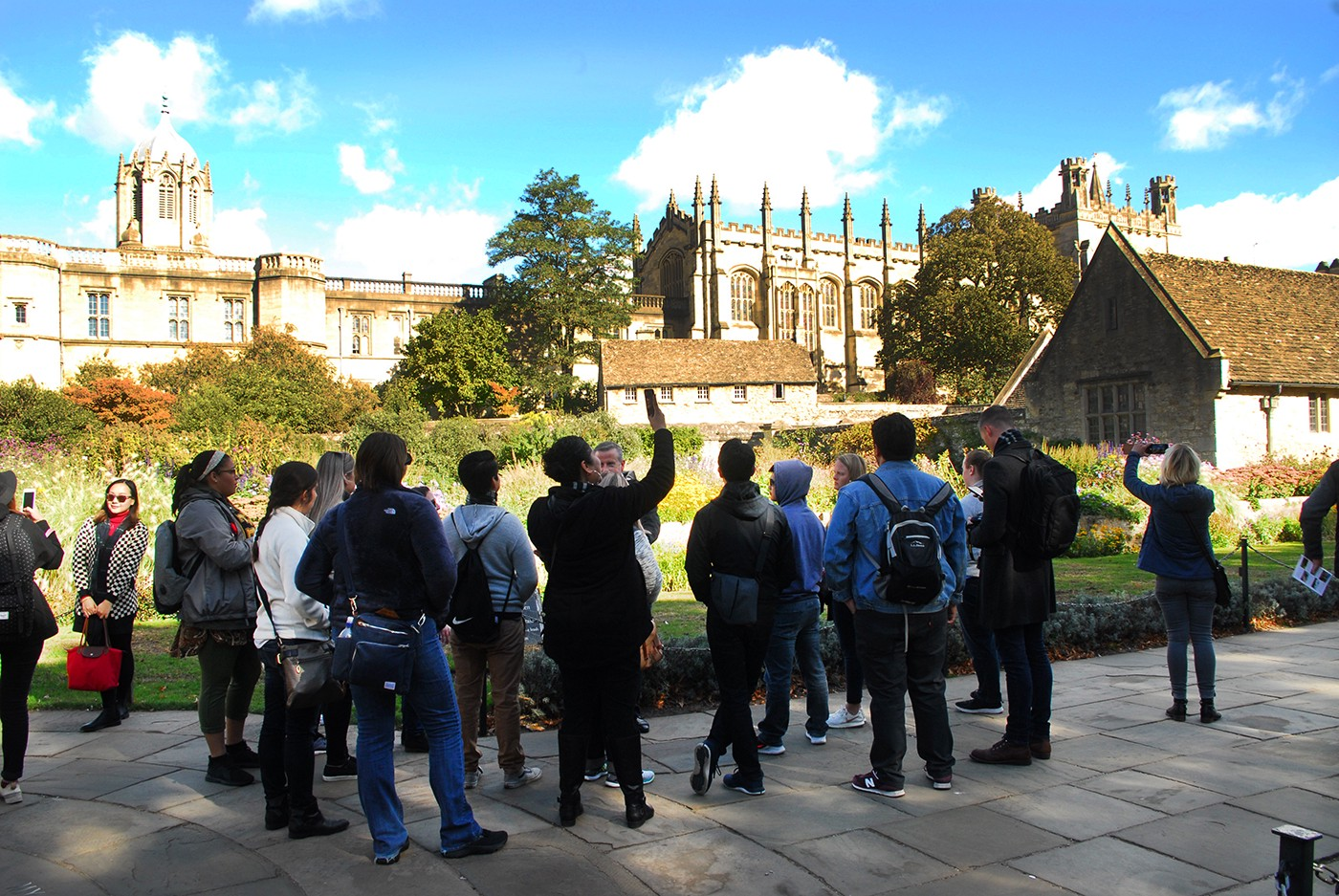 A group of tourists listening to a tour guide in the gardens of an Oxford college
