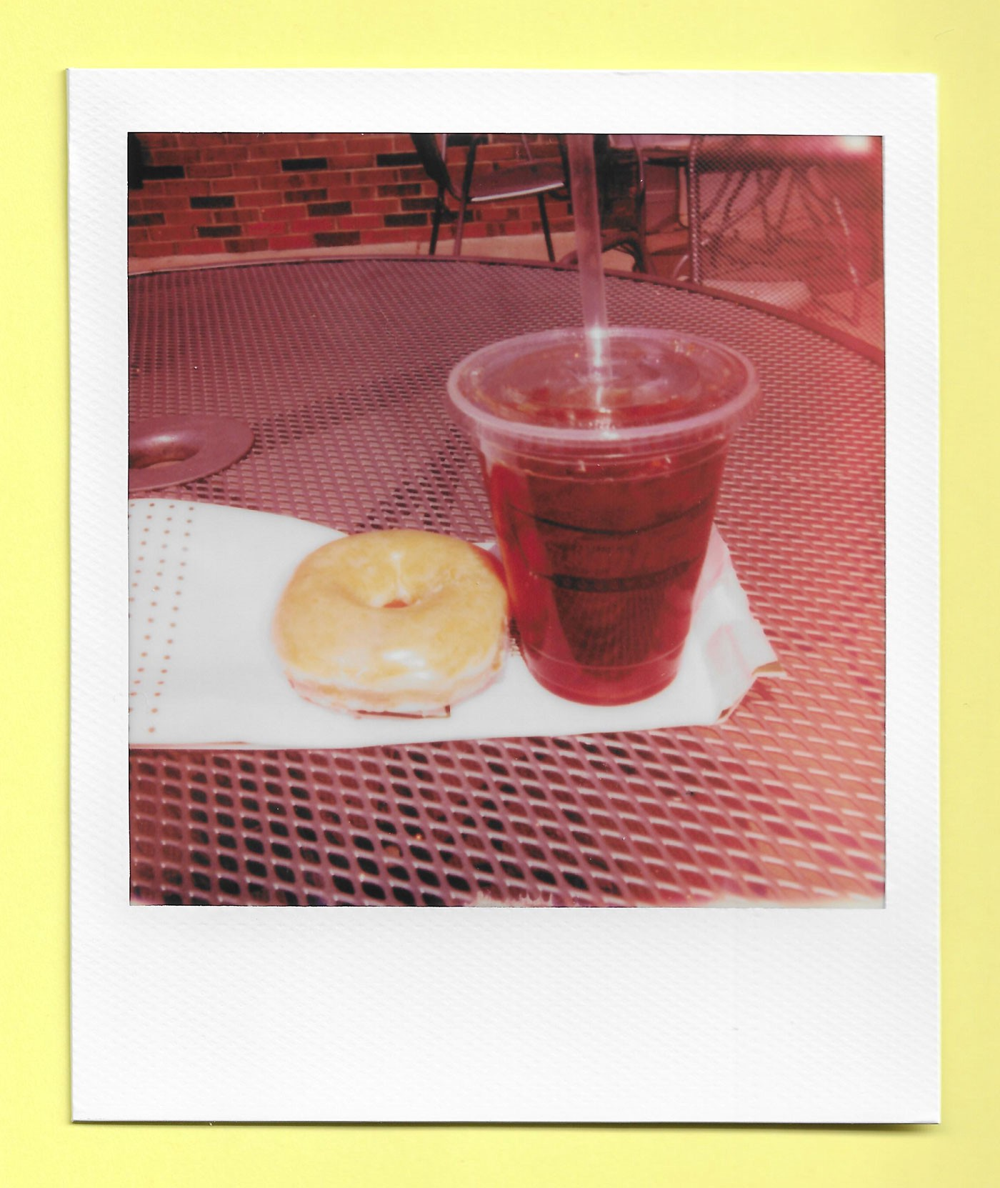 A donut and a plastic cup of iced tea sitting on a table