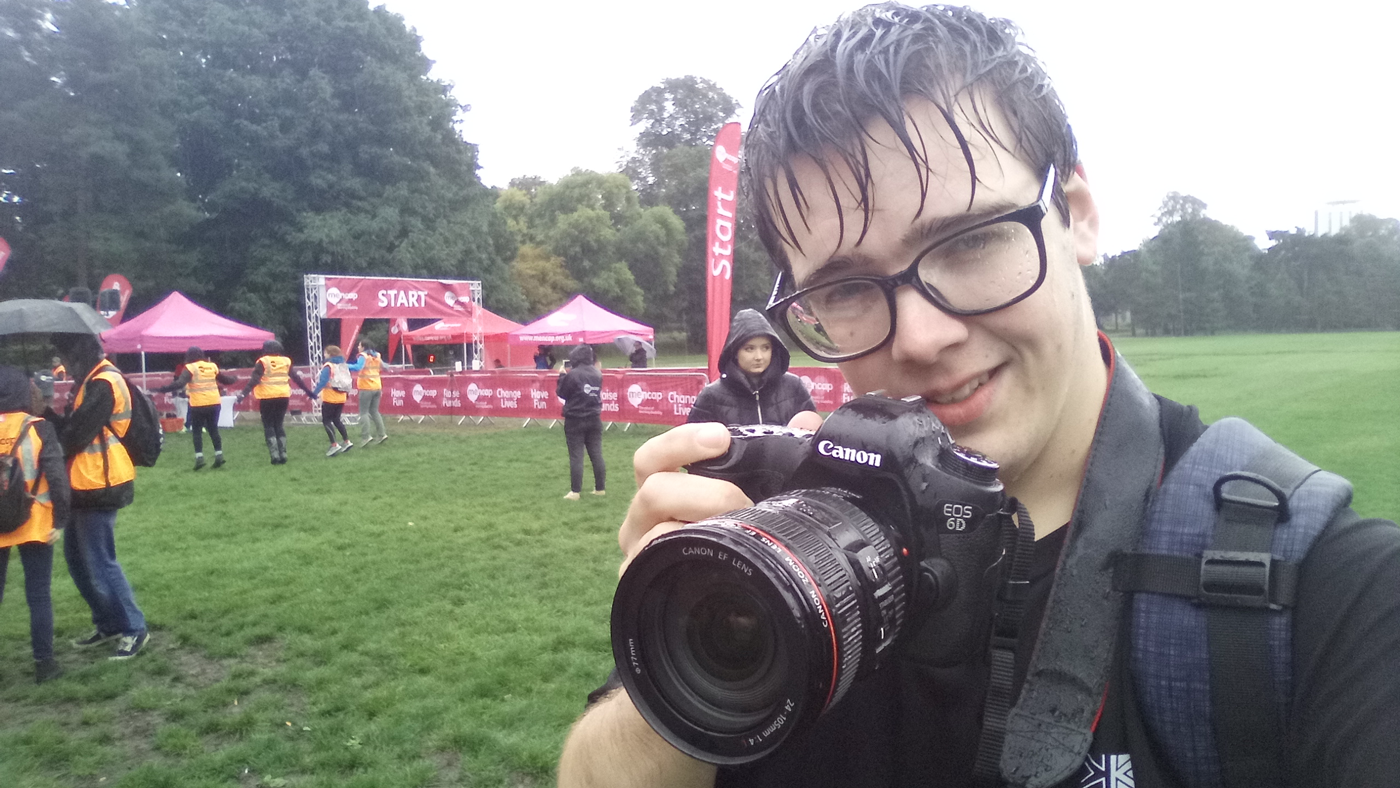 A boy holing a big DSLR camera, in the rain.