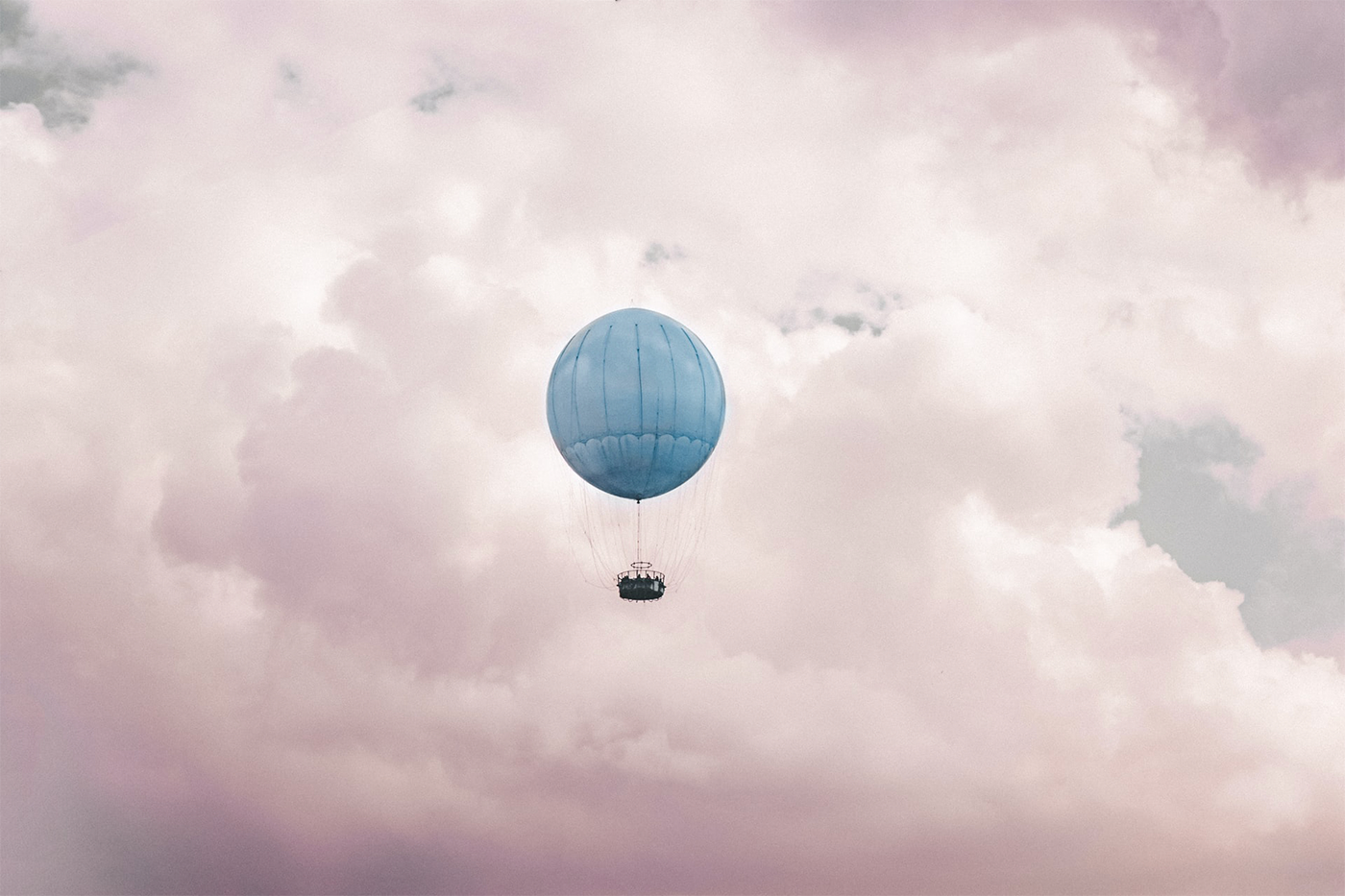 A hot air balloon floating through pink and pastel clouds.