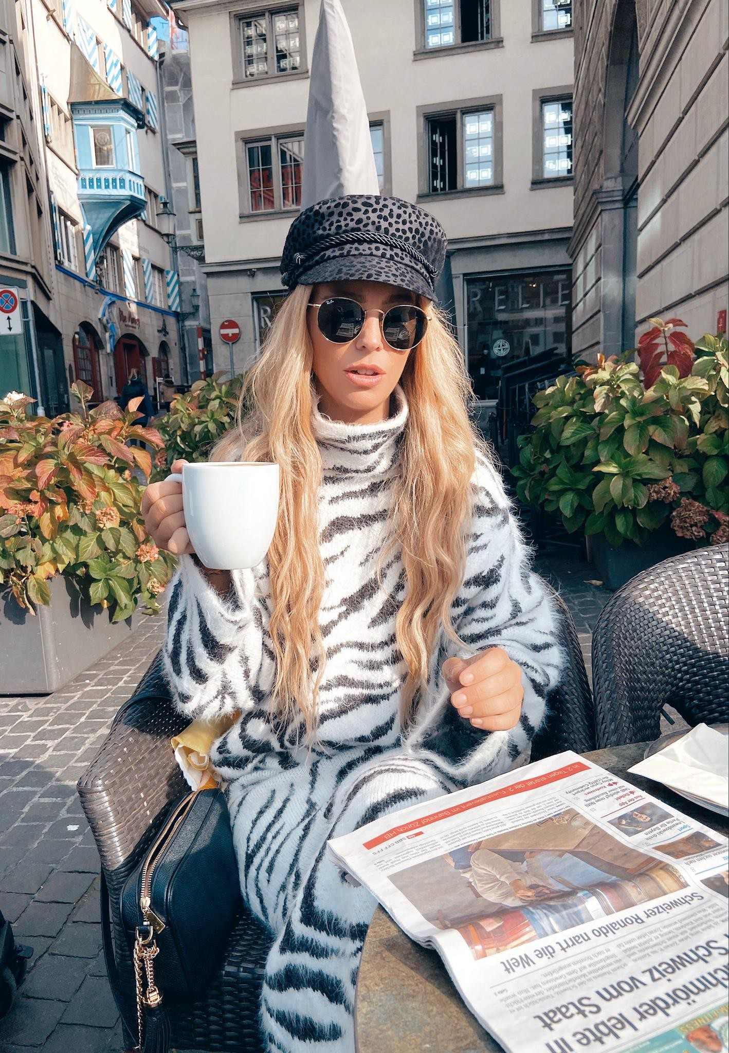 a woman sipping coffee in switzerland wearing animal print dress