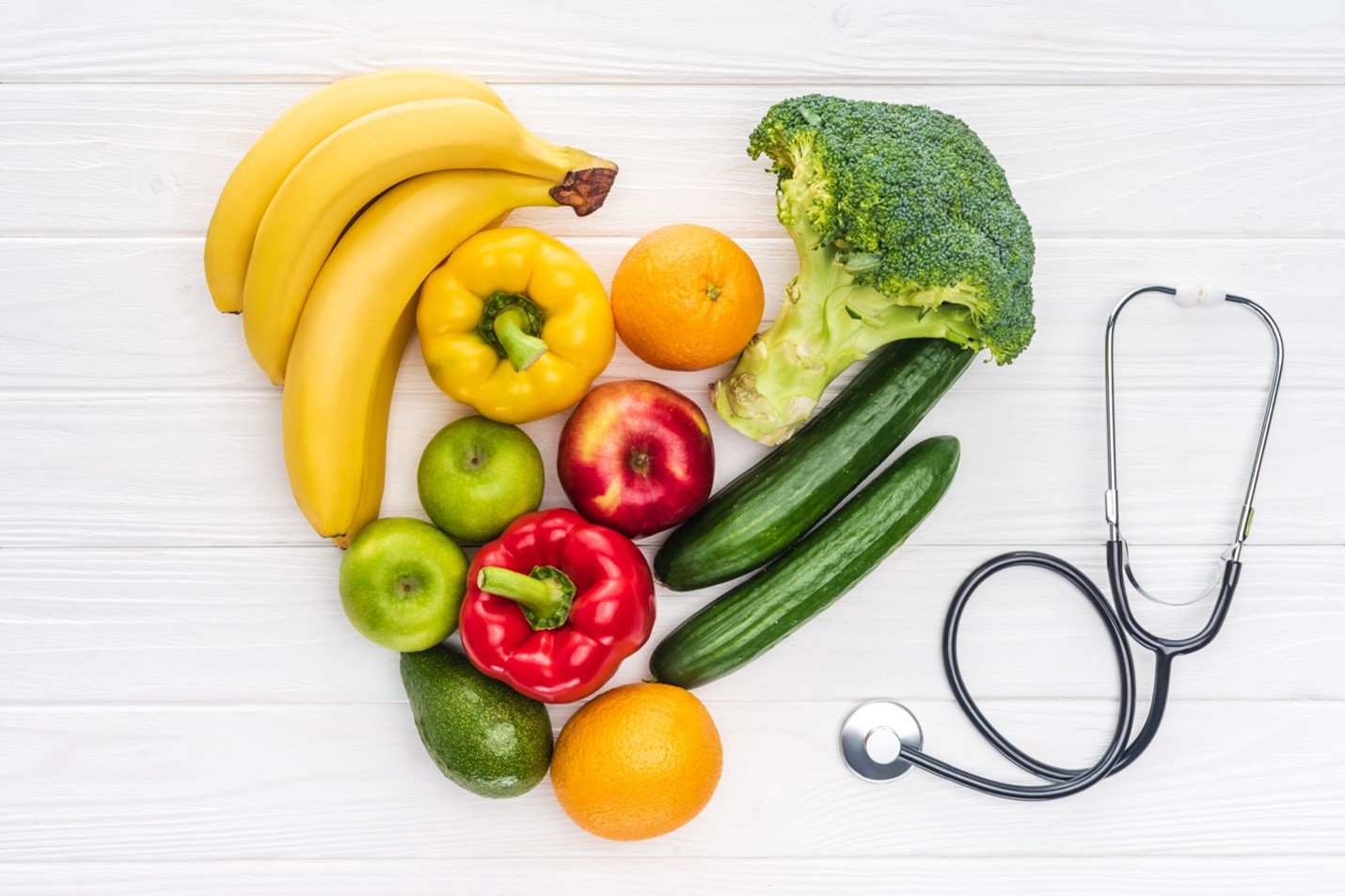 Fruits, vegetables and a stethoscope on a table
