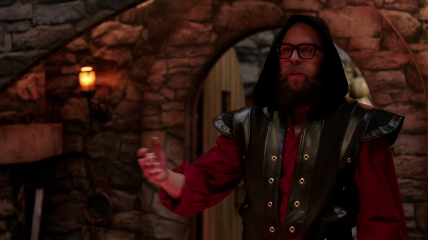A white man with glasses and a beard wears a leather vest and medieval-style shirt with a hood pulled up over his head. He's gesturing as he speaks.