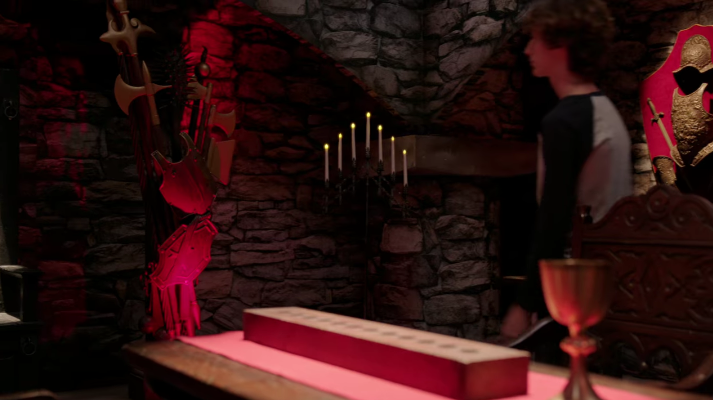 A white mother and her two sons walk into a medieval-themed escape room. The walls are stone and there are decorative items like a candelabra with fake candles, a suit of armor, a wooden table, and more.