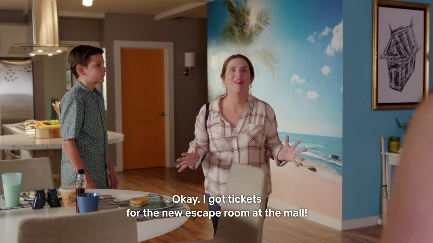 """A white woman spreads her fingers as she speaks to people offscreen excitedly. She's saying, """"Okay, I got tickets for the new escape room at the mall!"""""""