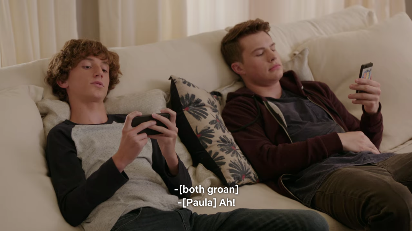 """Two white teen boys lounge on a sofa. Both are looking at their phones. It's subtitled, """"[Both groan.]"""" and """"Paula: Ah!"""""""