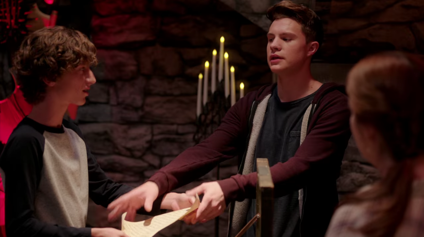 One teen boy holds the scroll, and the other reaches for it.