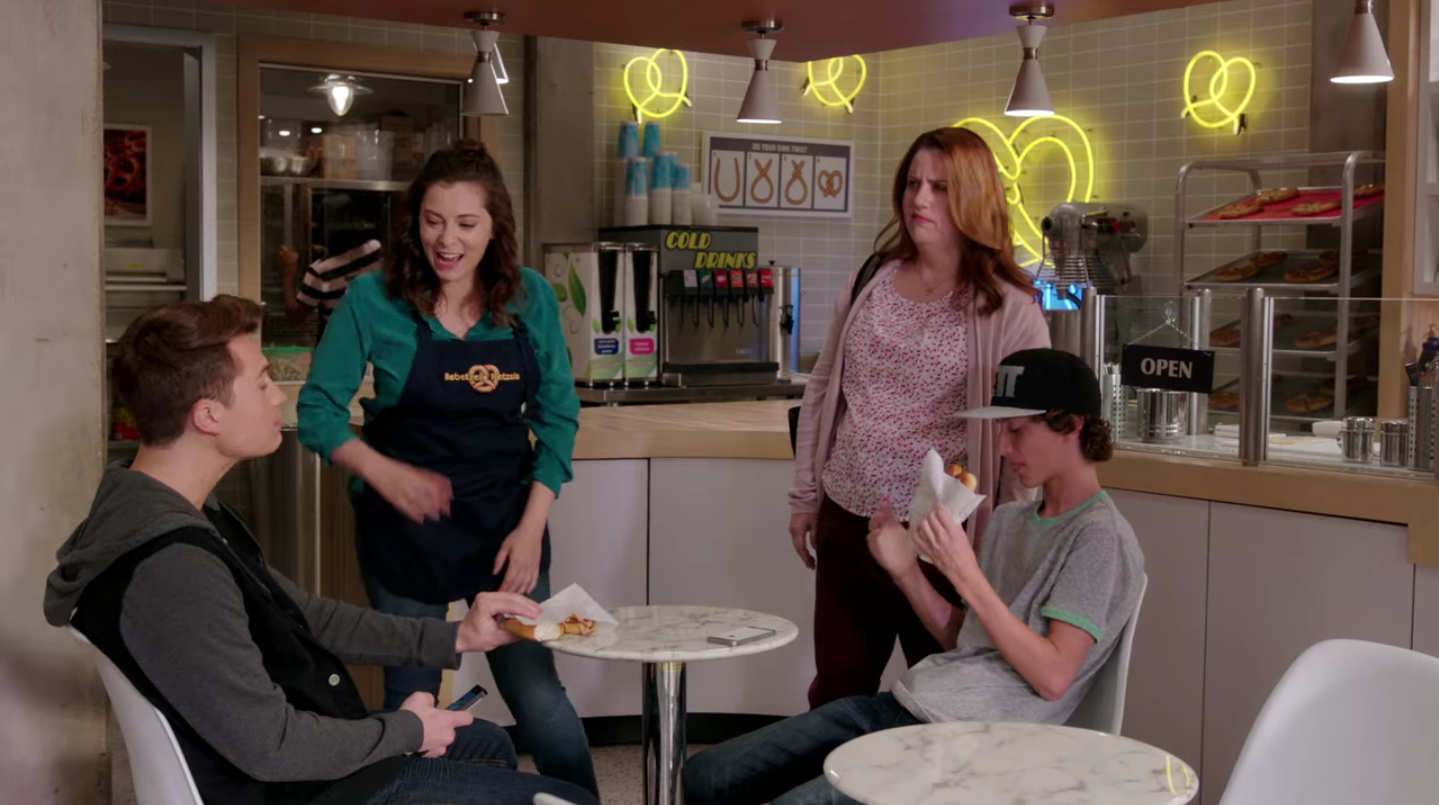 A scene in a small, mall pretzel shop. Two white women are standing next to two white boys seated at a table. One woman is wearing a pretzel shop apron and smiling. The boys look bored.