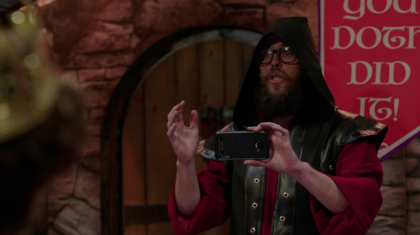 The escape room attendant, a white man with a beard and glasses, wearing a medieval-looking vest and shirt, holds up a phone to take a group photo. He's raising his hand to gesture for the group to stand closer together