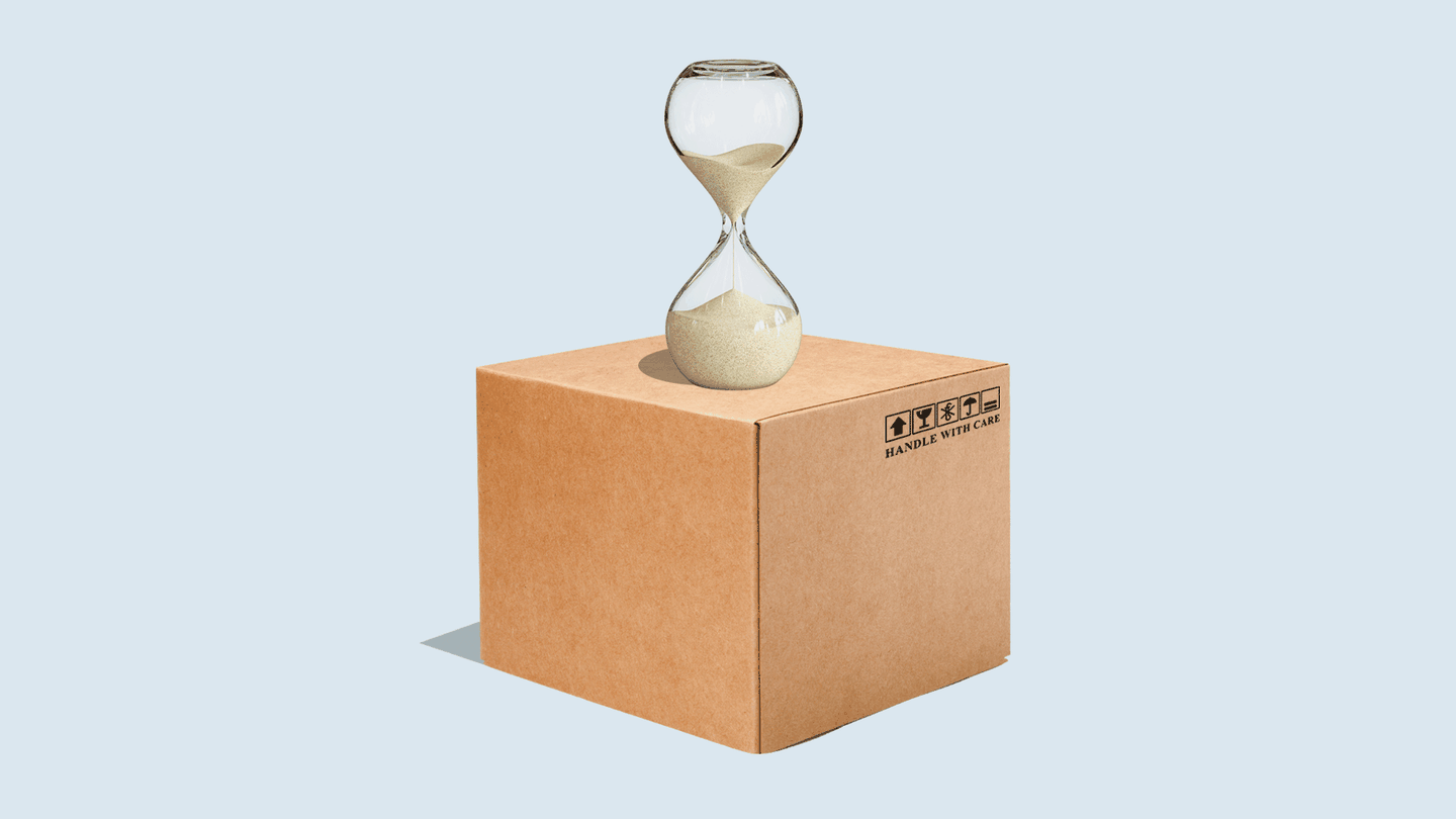 An hourglass with sand trickling down from the top section to the bottom, on top of a cardboard box.