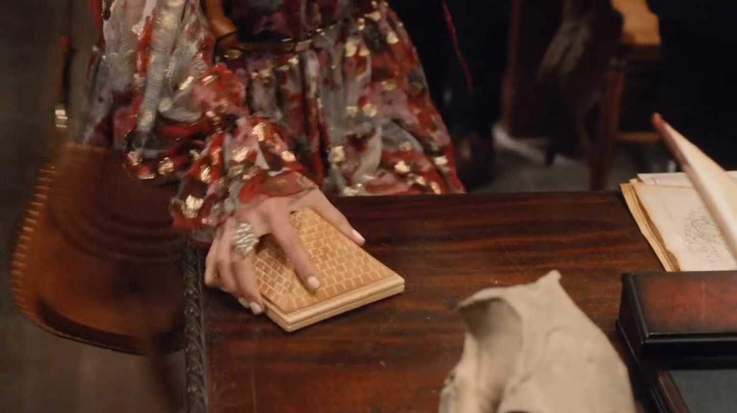 A woman's hand as it picks up a pyramid statuette on a desk