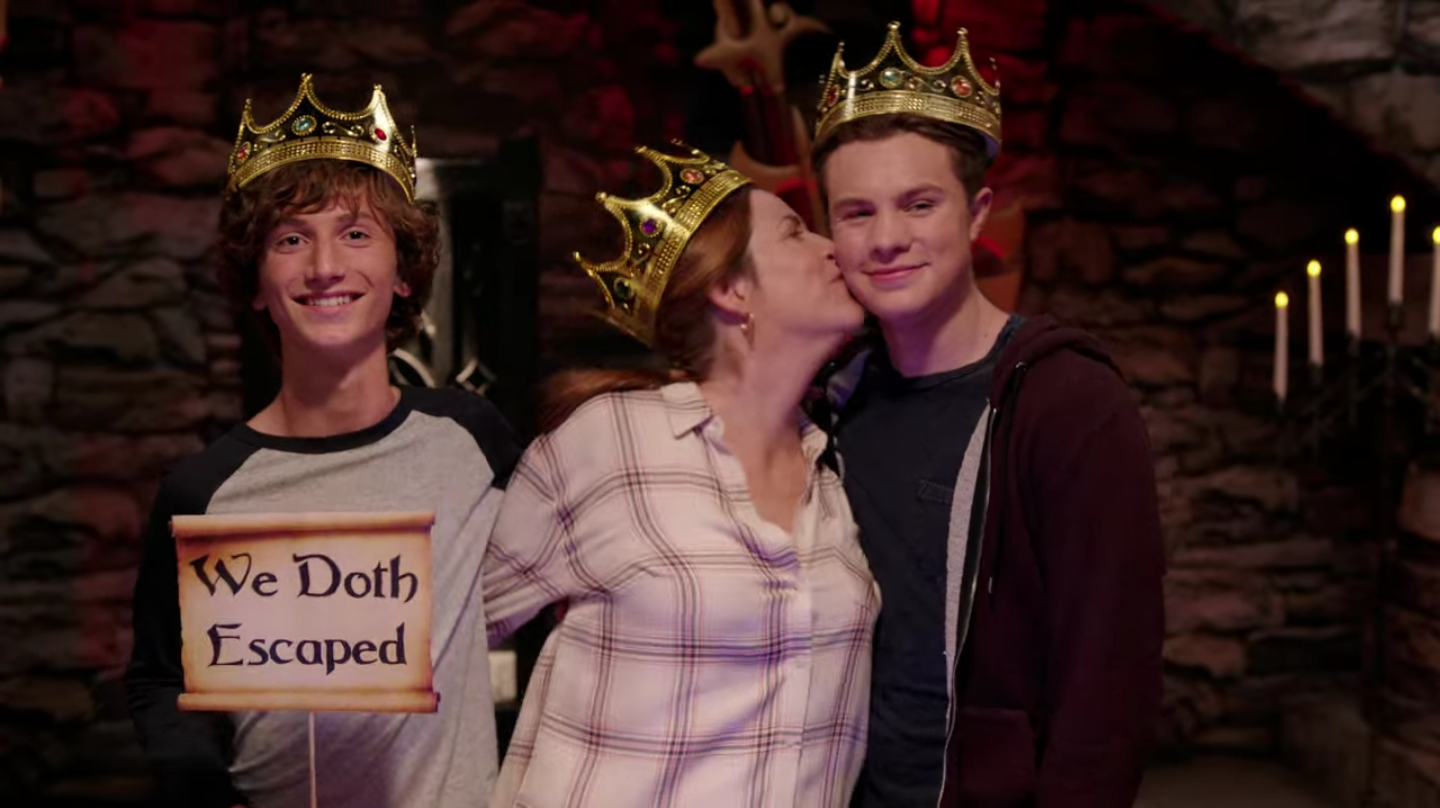 """A white woman stands next to her two teenage sons. All of them are wearing gaudy plastic crowns. One of the boys is holding up a little sign that says """"We doth escaped"""". The mother is leaning over to kiss her son on the cheek. All three are smiling happily."""