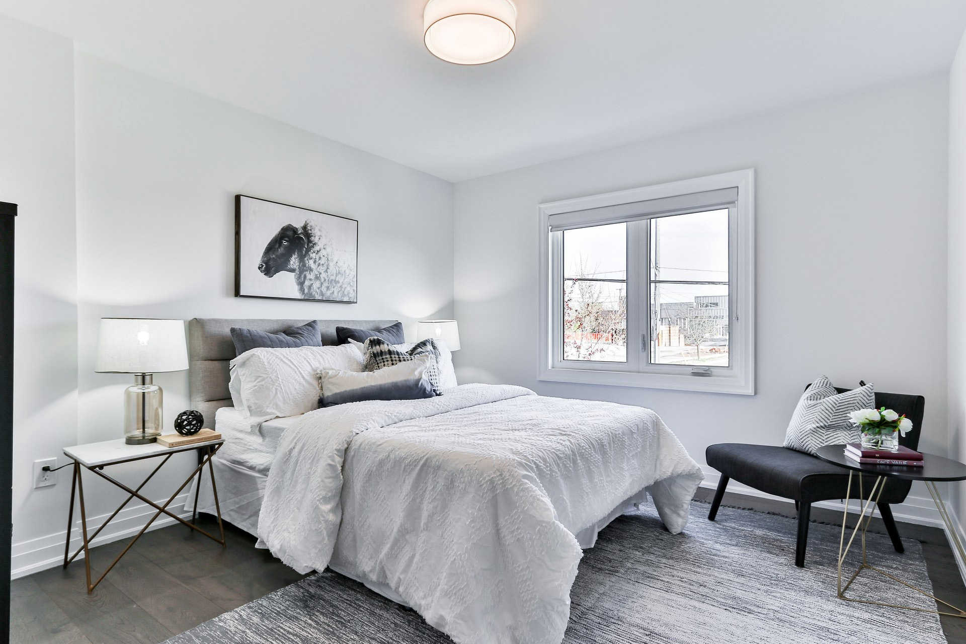 Modern white bedroom with double bed and black chair
