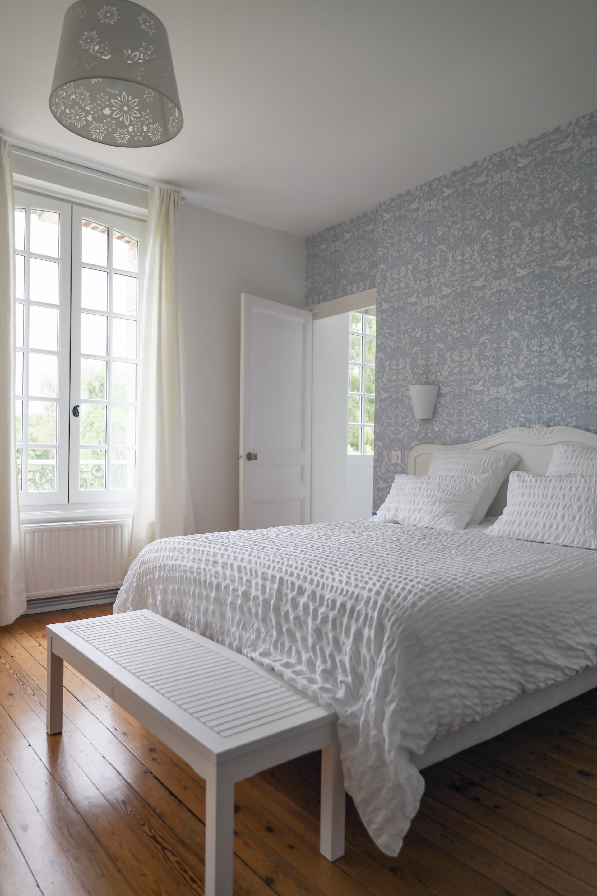 Double bed in a bedroom and pattern wallpaper