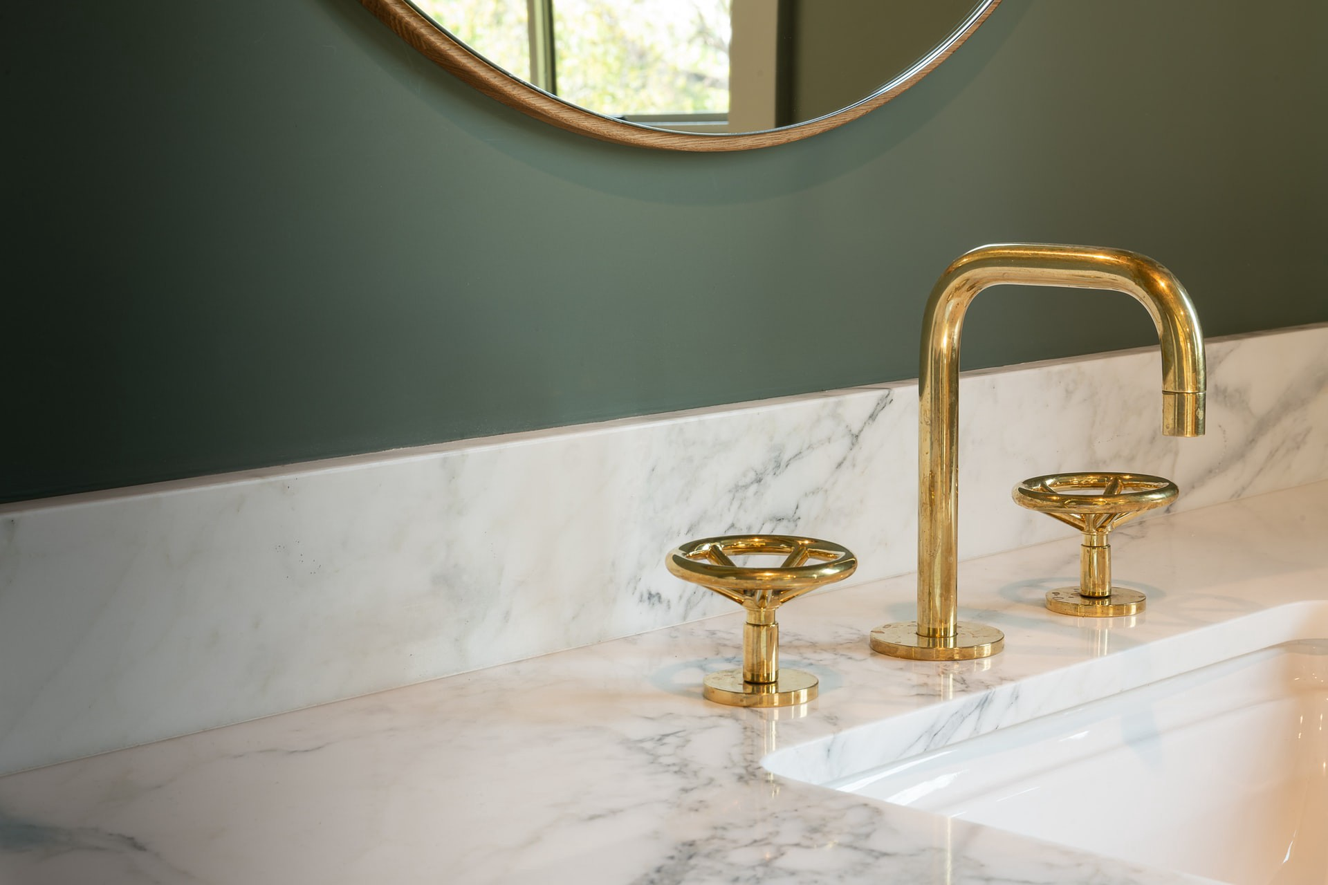 Sink with a marble countertop and gold faucet