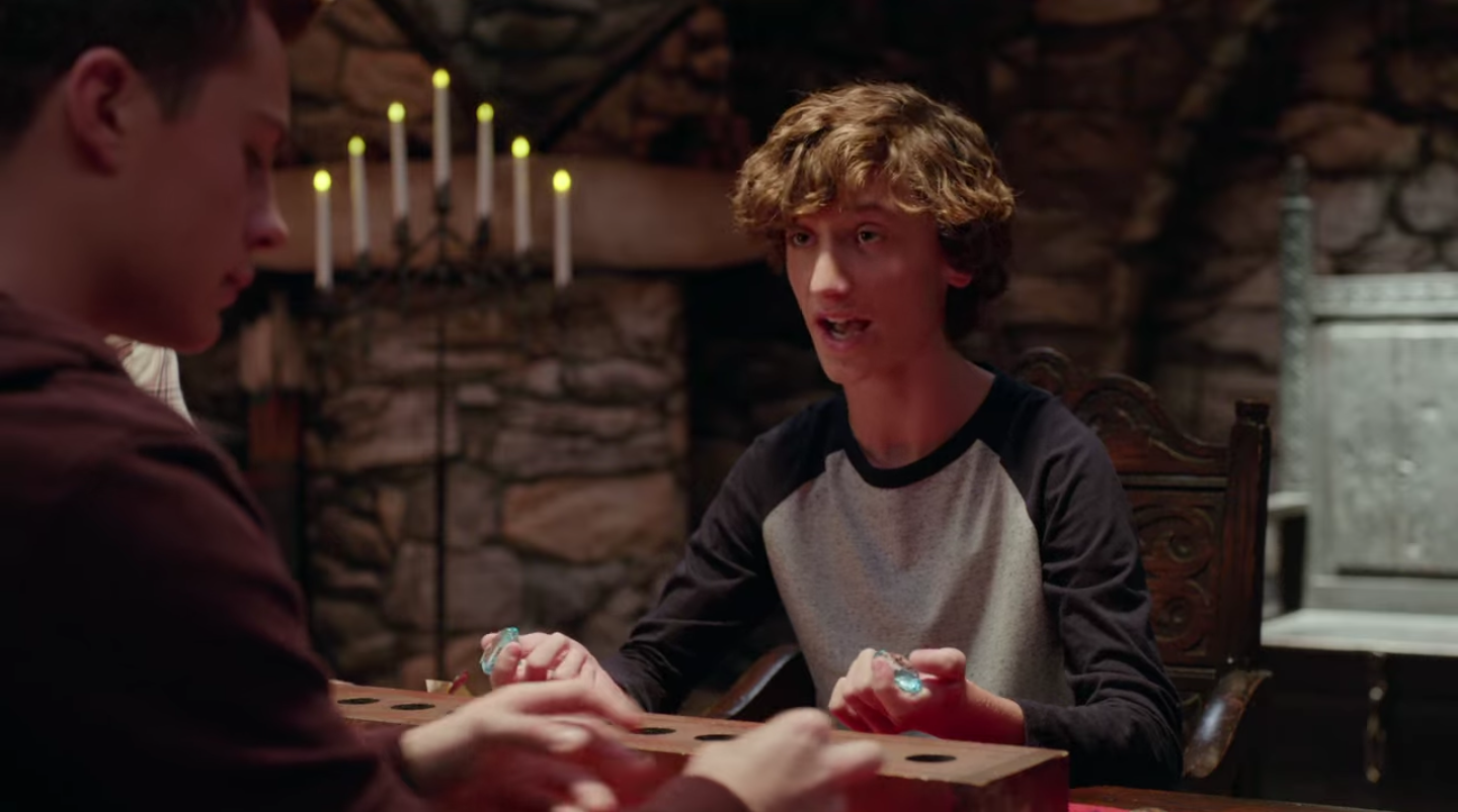 A white teen boy sits across from his brother at a table. He's holding plastic gemstones in both hands as they talk.