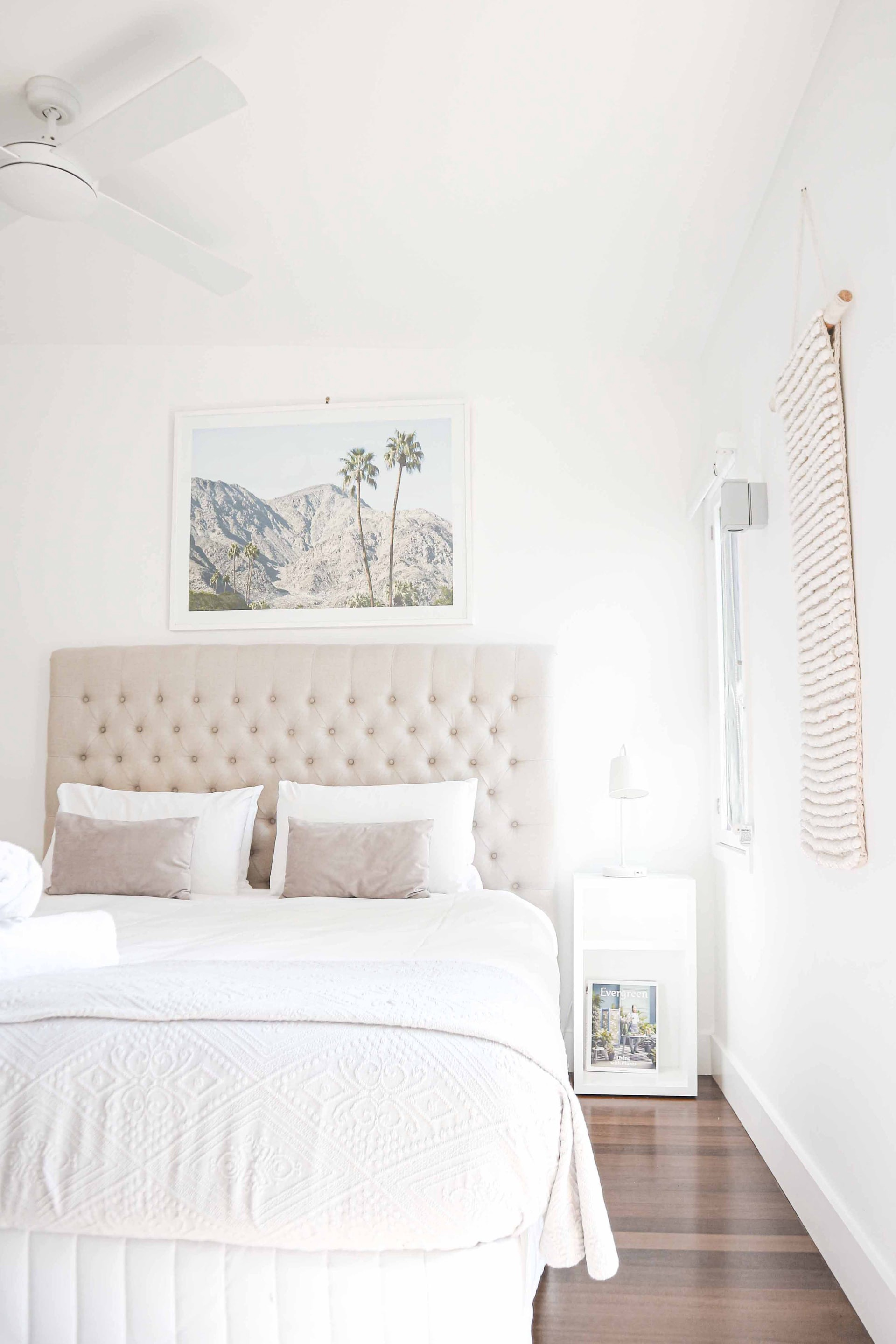 Light bedroom with double bed and side table