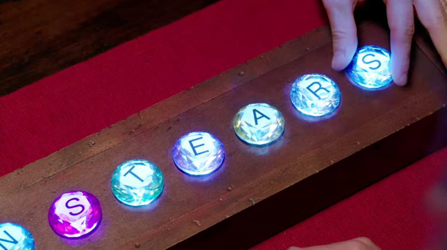 """A row of plastic gemstones with letters on them. They spell out """"STEARS"""", or the end of """"DRAGON'S TEARS"""". They're lit from behind here."""