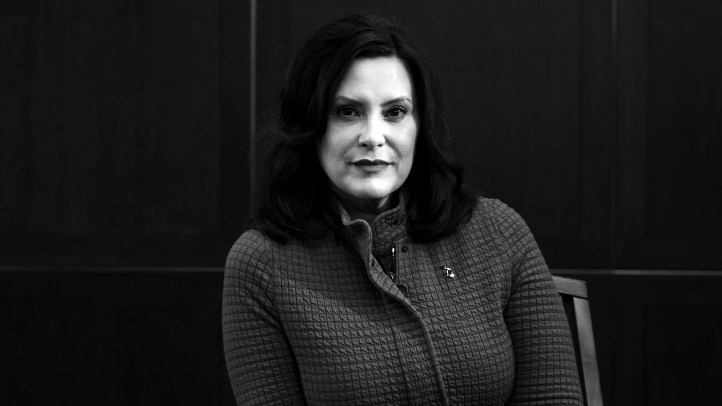Black-and-white photo of Gretchen Whitmer sitting on a chair, looking at the camera.