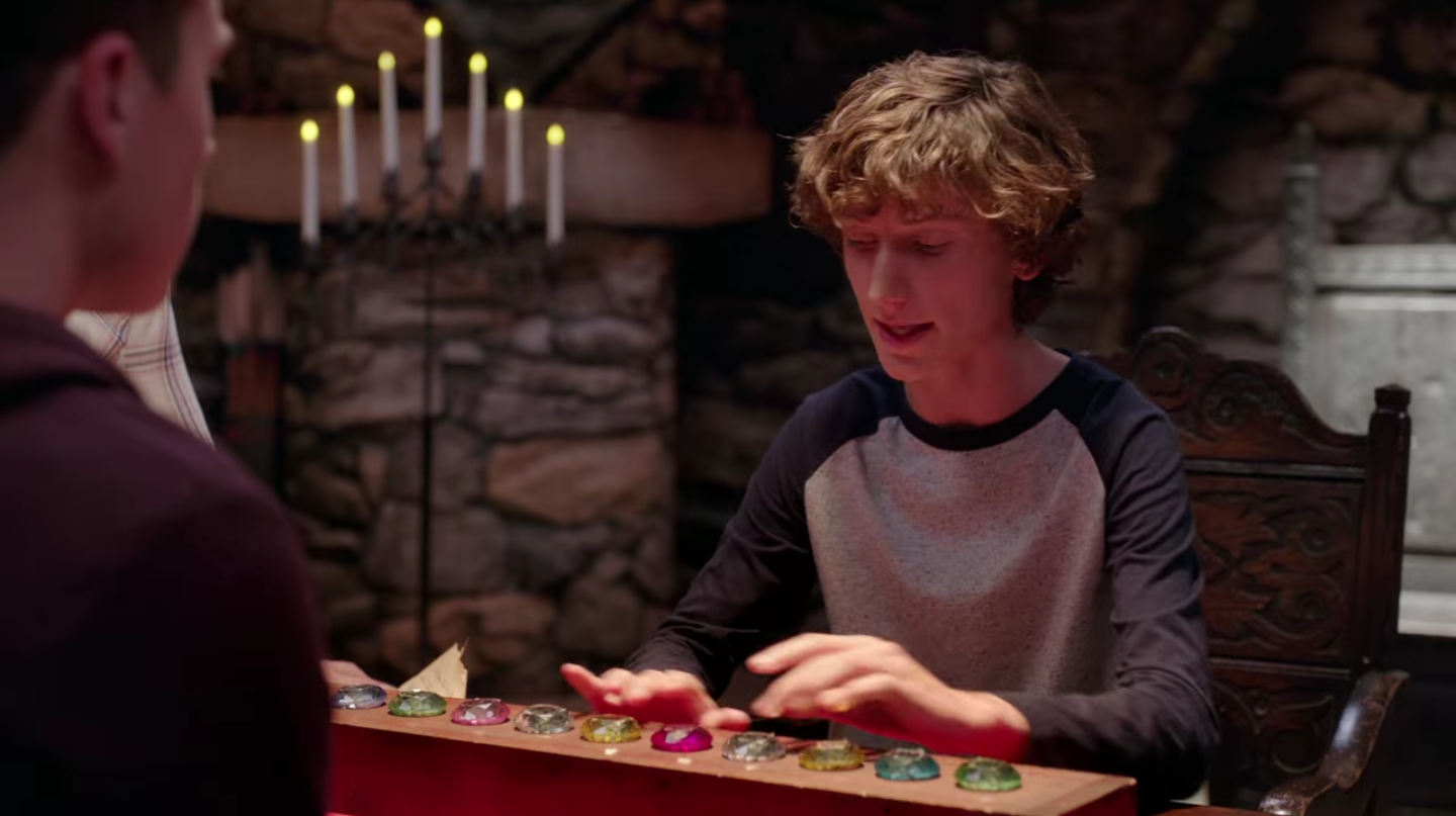 A white teen boy raises his hands over a row of colorful plastic gemstones as he contemplates their order