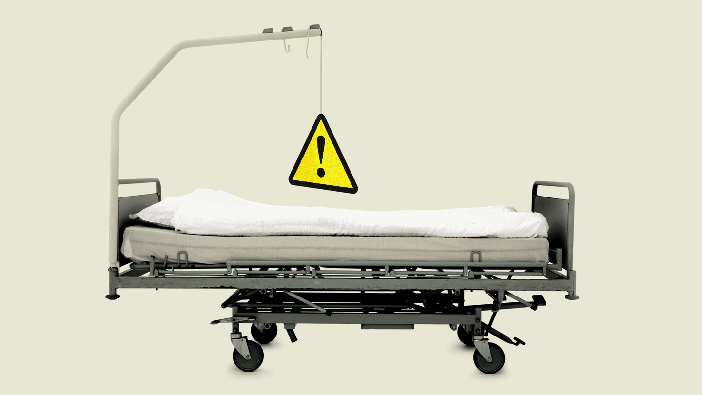 Side-view of a hospital bed with a metal bar above it; hanging from it is a triangular yellow caution sign.
