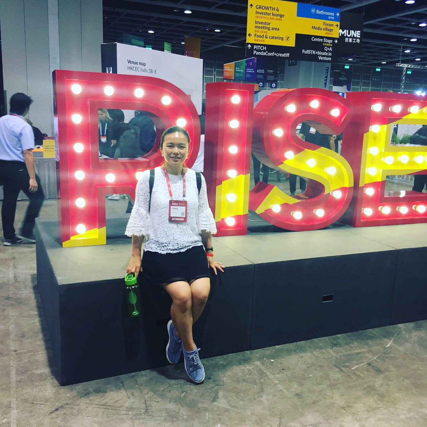 A picture of me with RISE sign on the background at RISE Conference 2019