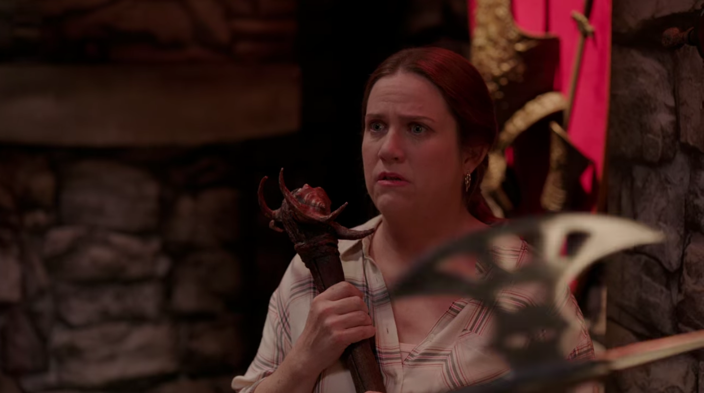 The white woman clasps her medieval weapon to her chest, looking forlorn as she stares into the middle distance.