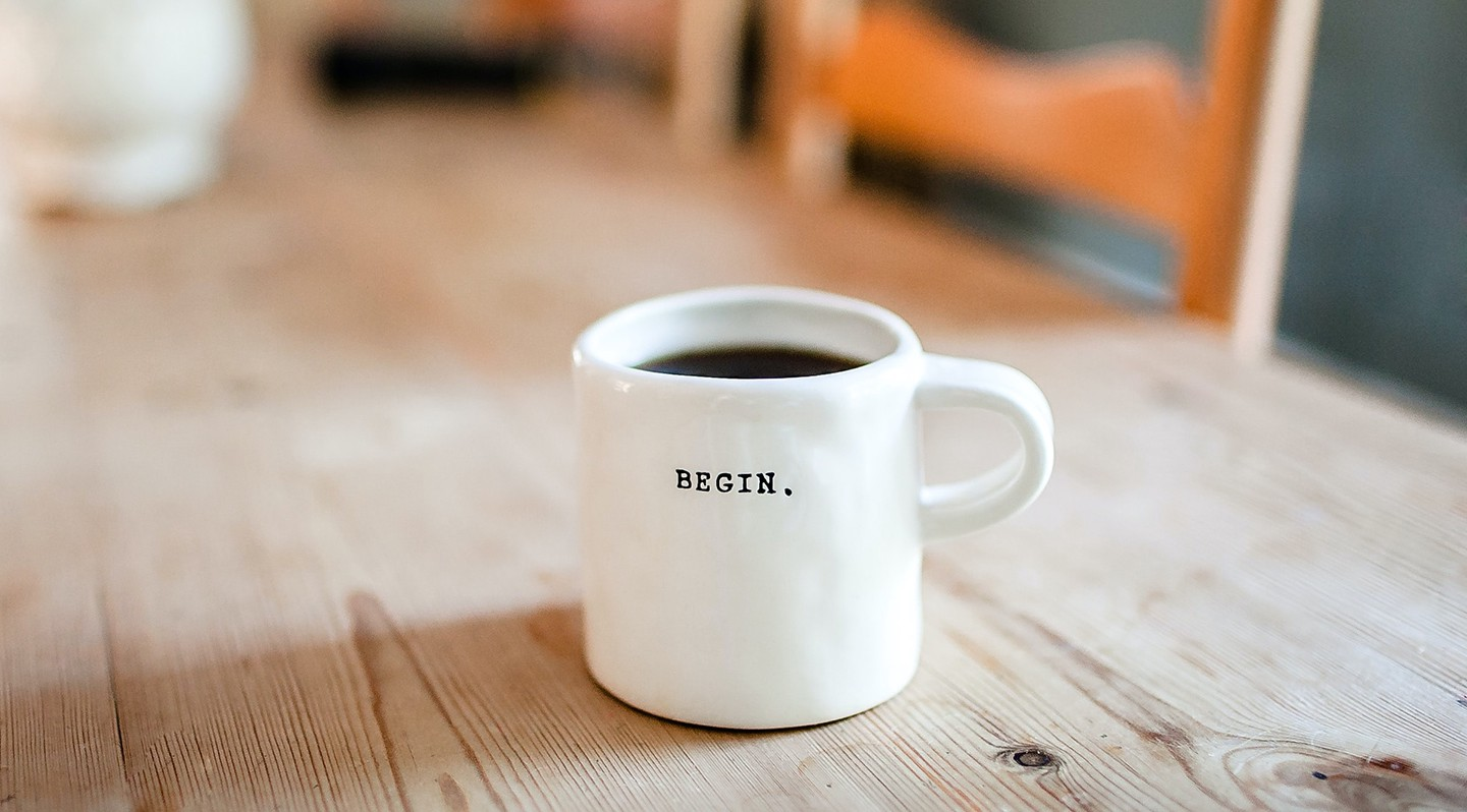 White coffee cup that says BEGIN on a wooden coffee table
