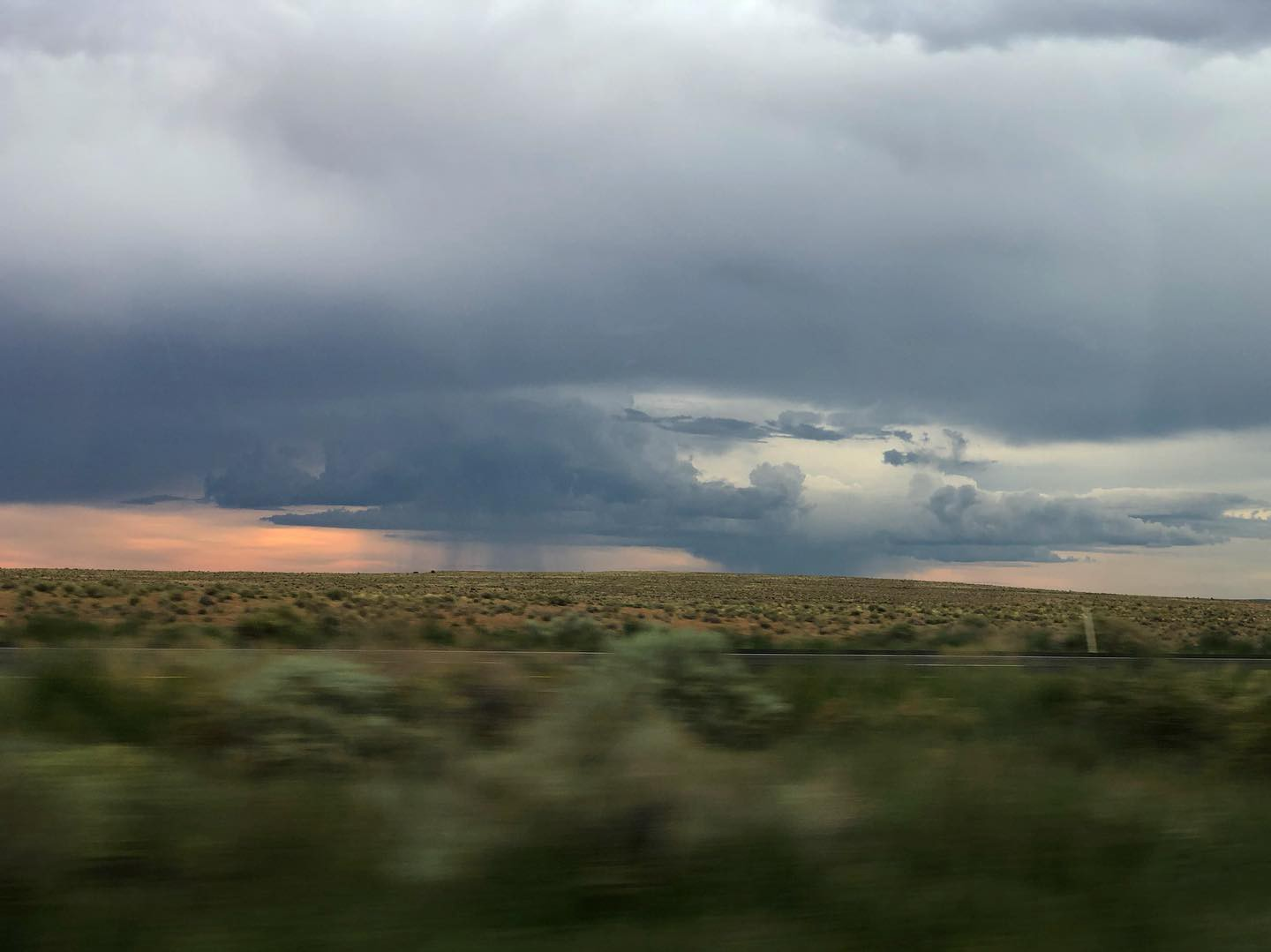 Photo from a moving car,  foreground is blurred, and beyond fields of sage brush, there is a sunset and two rain storms.