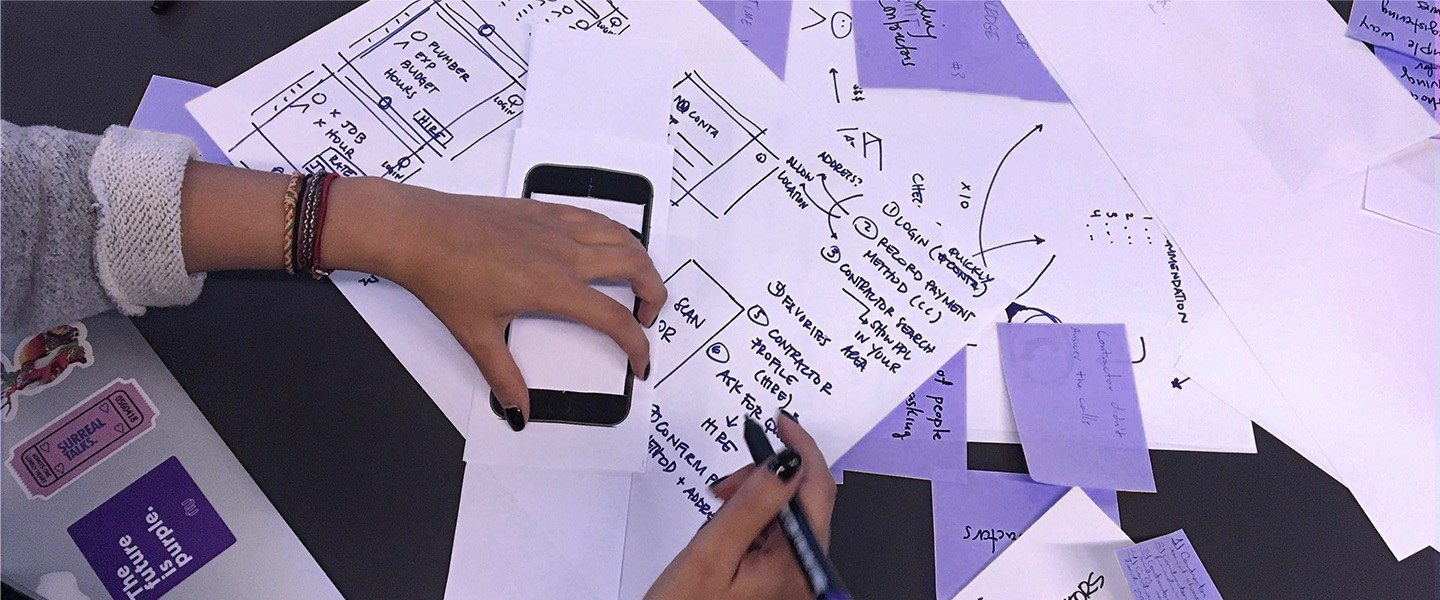 Pieces of paper containing wireframes and notes scattered on a desk; a person holding a pen.