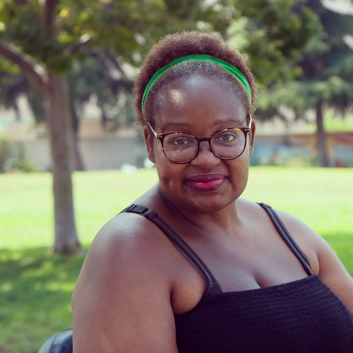A Black woman with short hair, a green headband, brown-framed glasses, a black tank top & pink lipstick smiles cutely.
