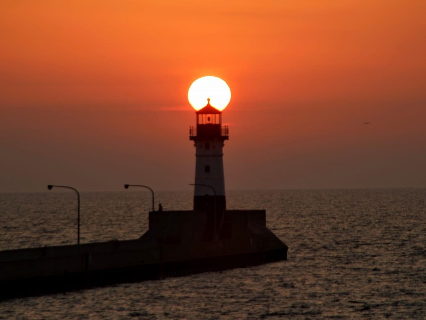 The Sun rising behind the lighthouse on the Duluth Lighthouse on Lake Superior MN