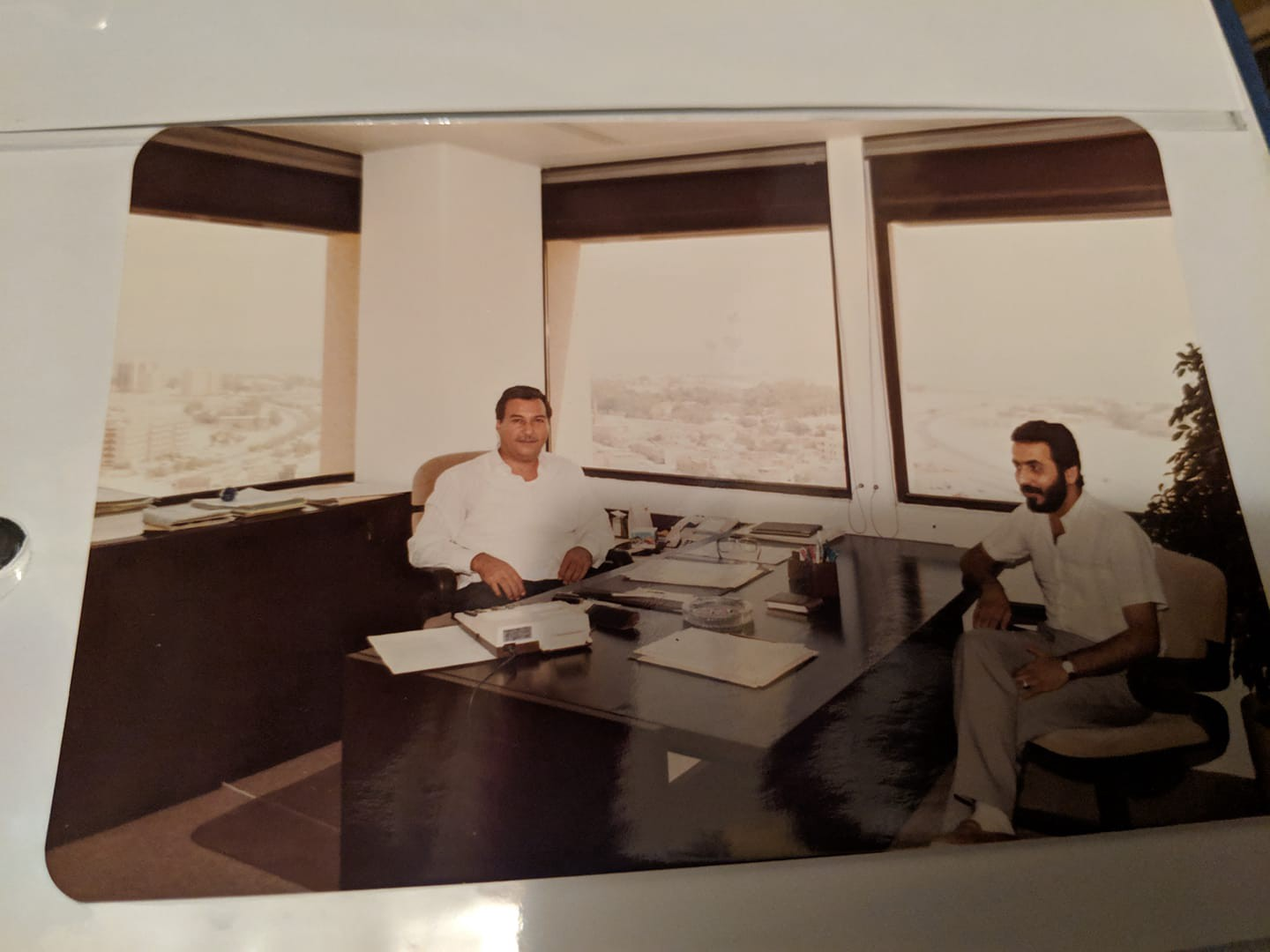 My father sits behind an office desk with a colleague sitting in front of the desk. Several windows are behind the desk.