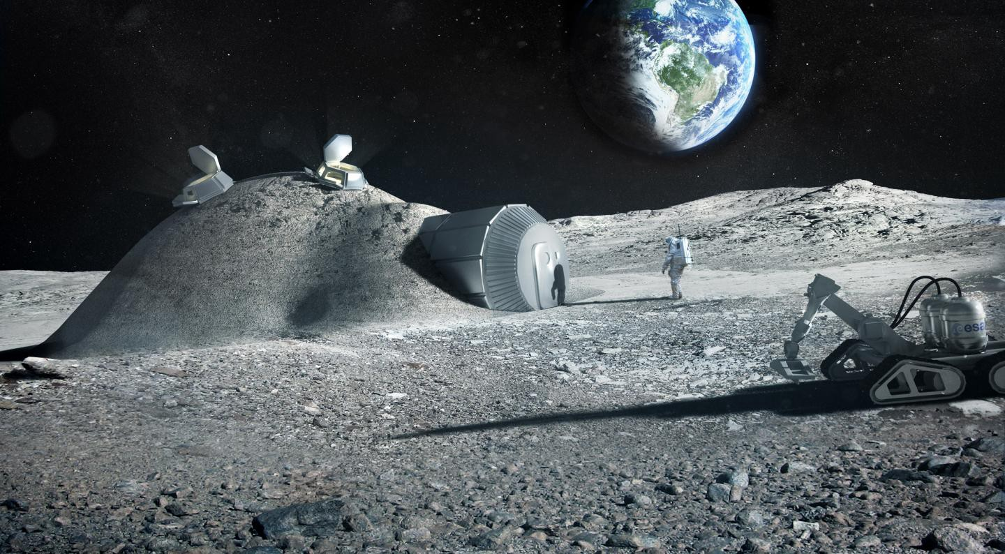 An astronaut walks outside a small lunar colony with a 3D printer seen on the side.