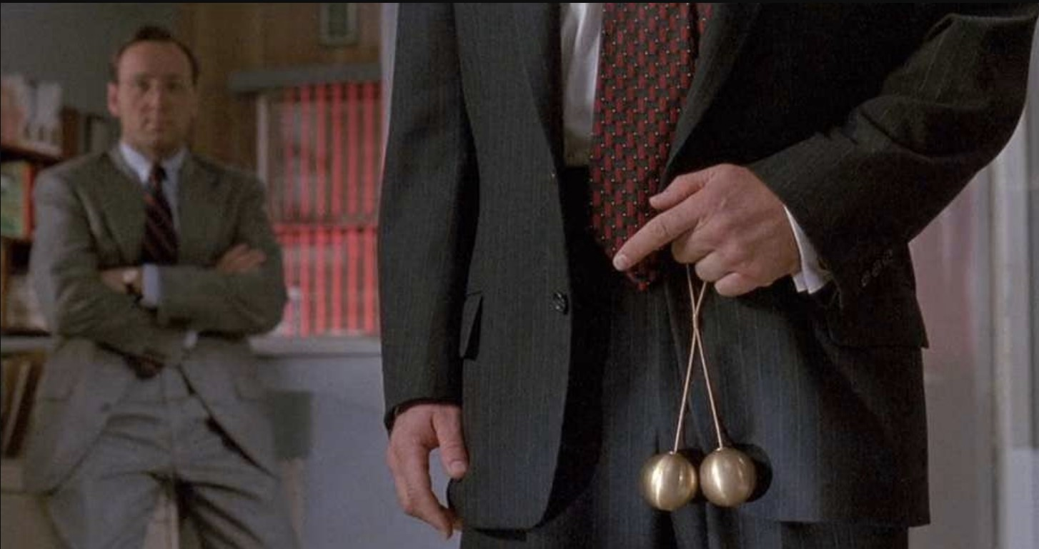 Scene from the movie Glengarry Ross — Alec Balding holding brass balls in front of his pants.