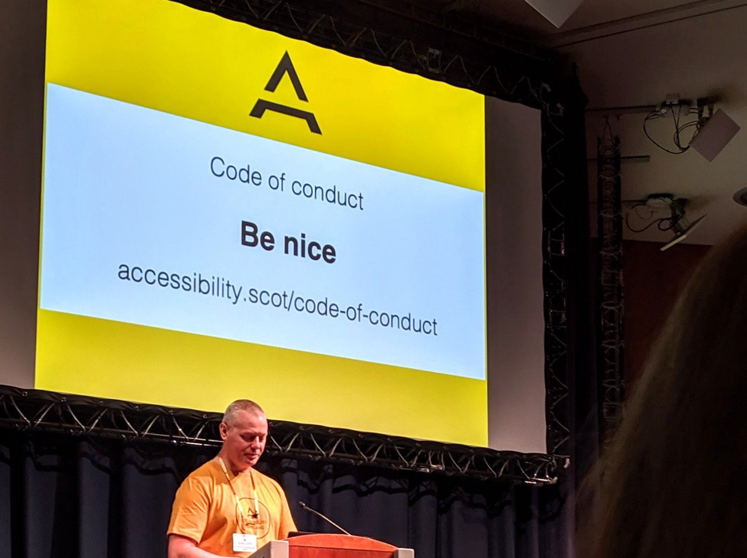 Kevin White — Organiser — on stage with the slide for the code of conduct saying: Be nice