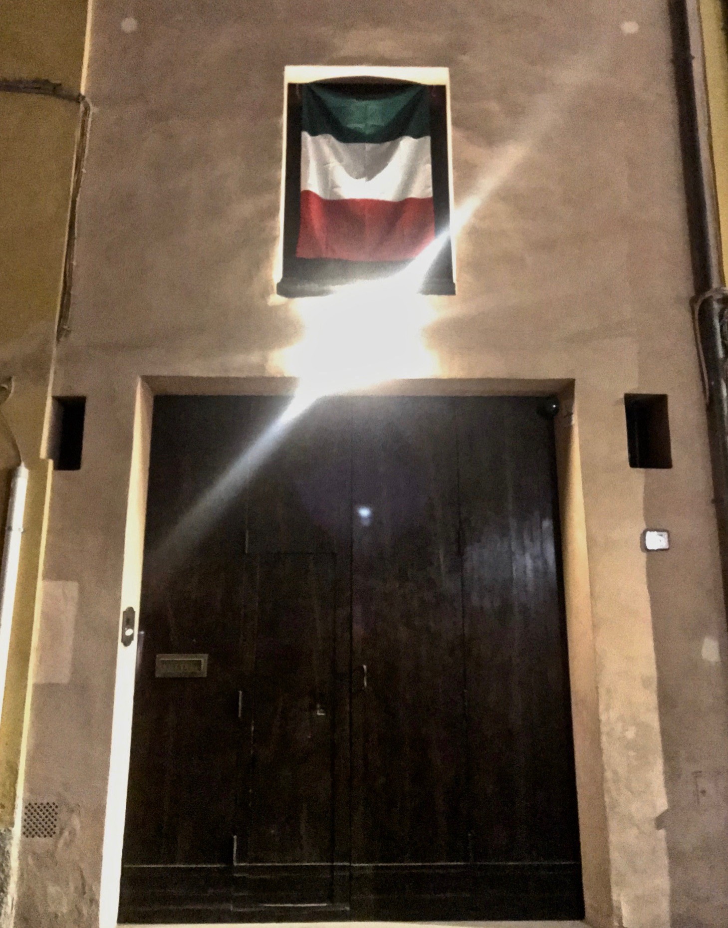 The Italian Flag Hanging Above An Apartment Door in Bologna, Italy. March 2020.