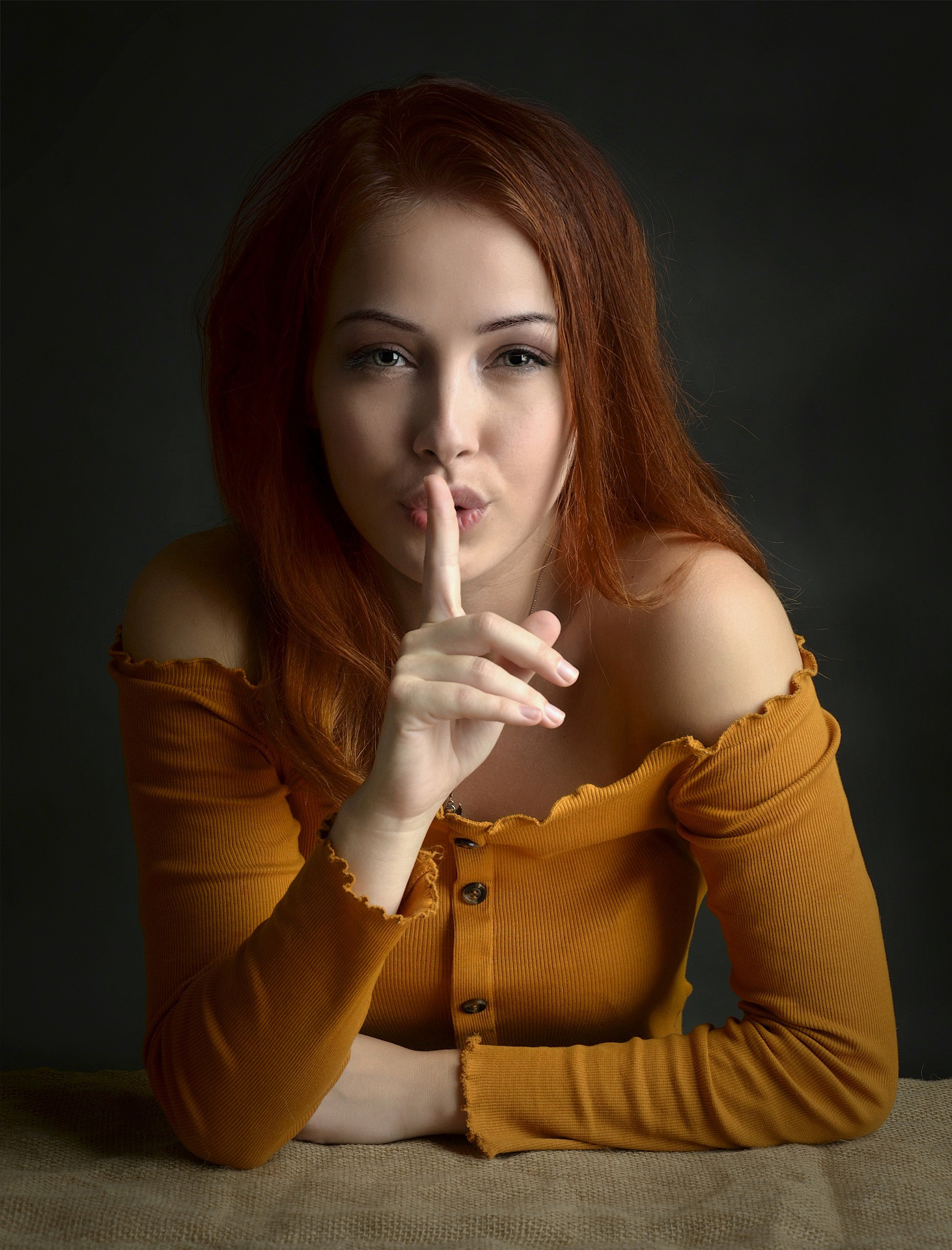 Image of a woman with finger to the lips, indicating silence.