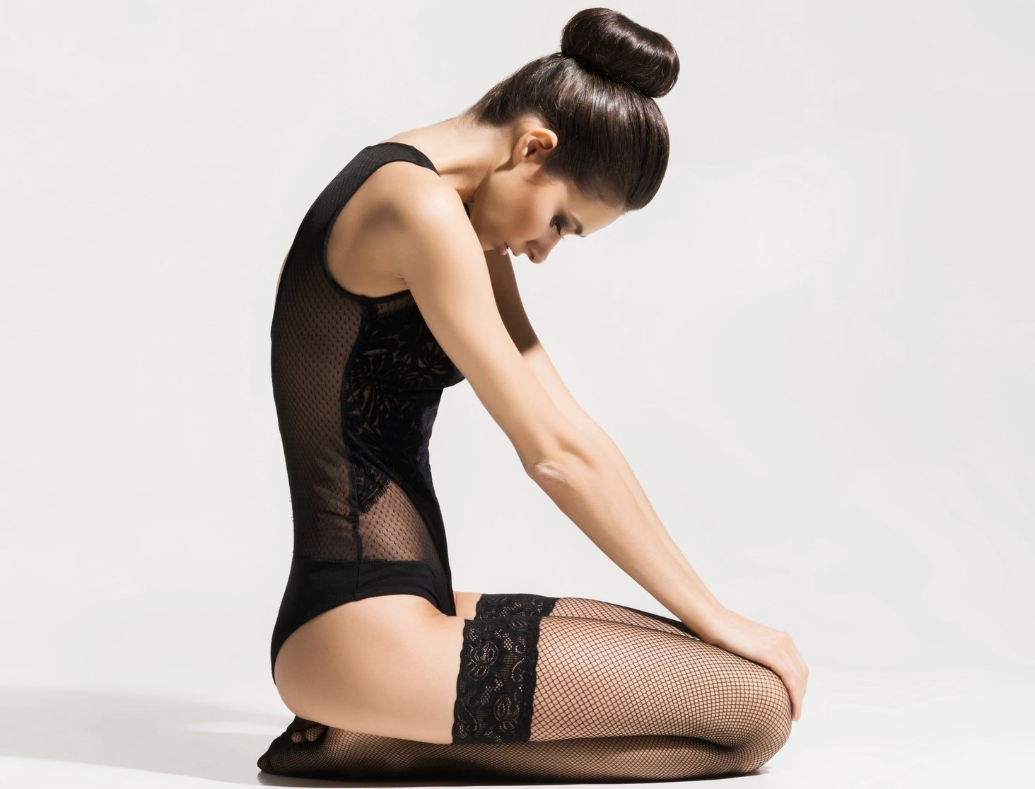 Woman kneeling in black hold up stockings and leotard lingerie
