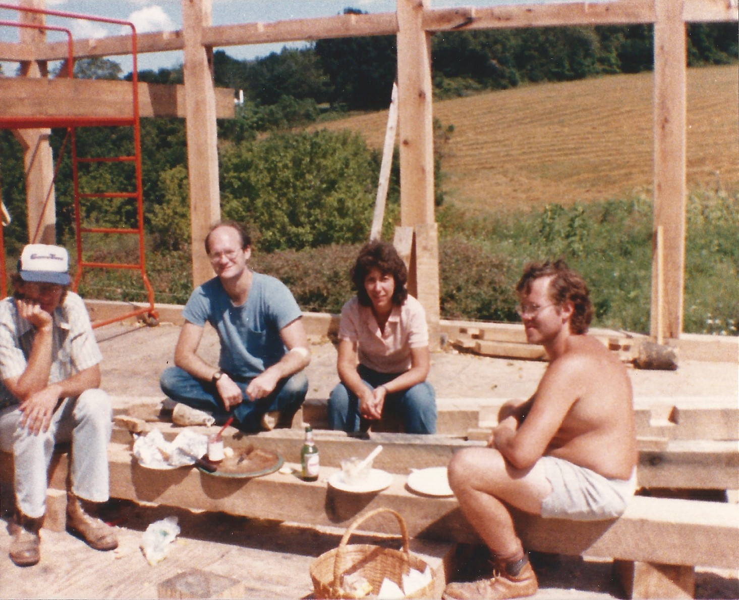 Author's father and friends enjoying lunch while sitting in a house under construction