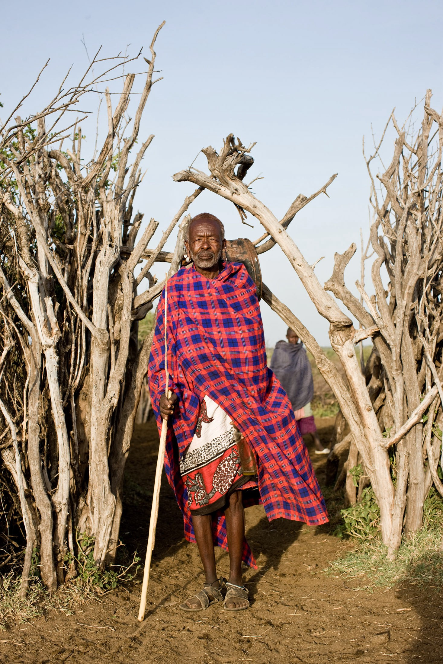 A Maasai elder wears a tartan wool shuka to ward off the early morning chill.