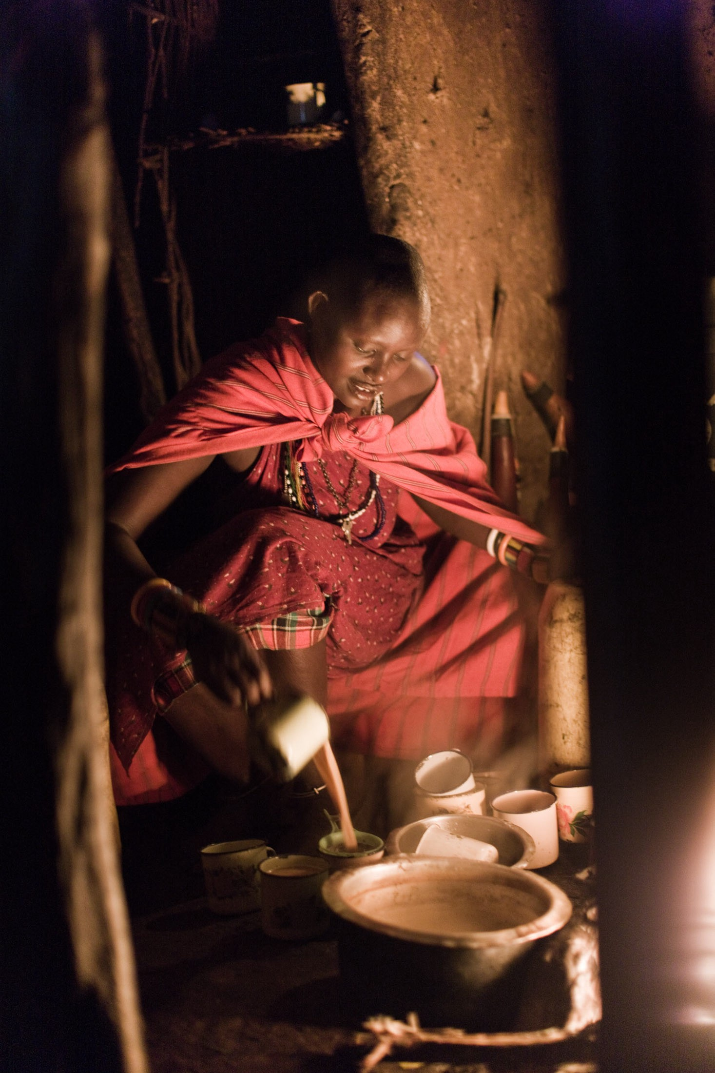 A Maasai woman makes morning tea with milk still warm from one of the village cows.