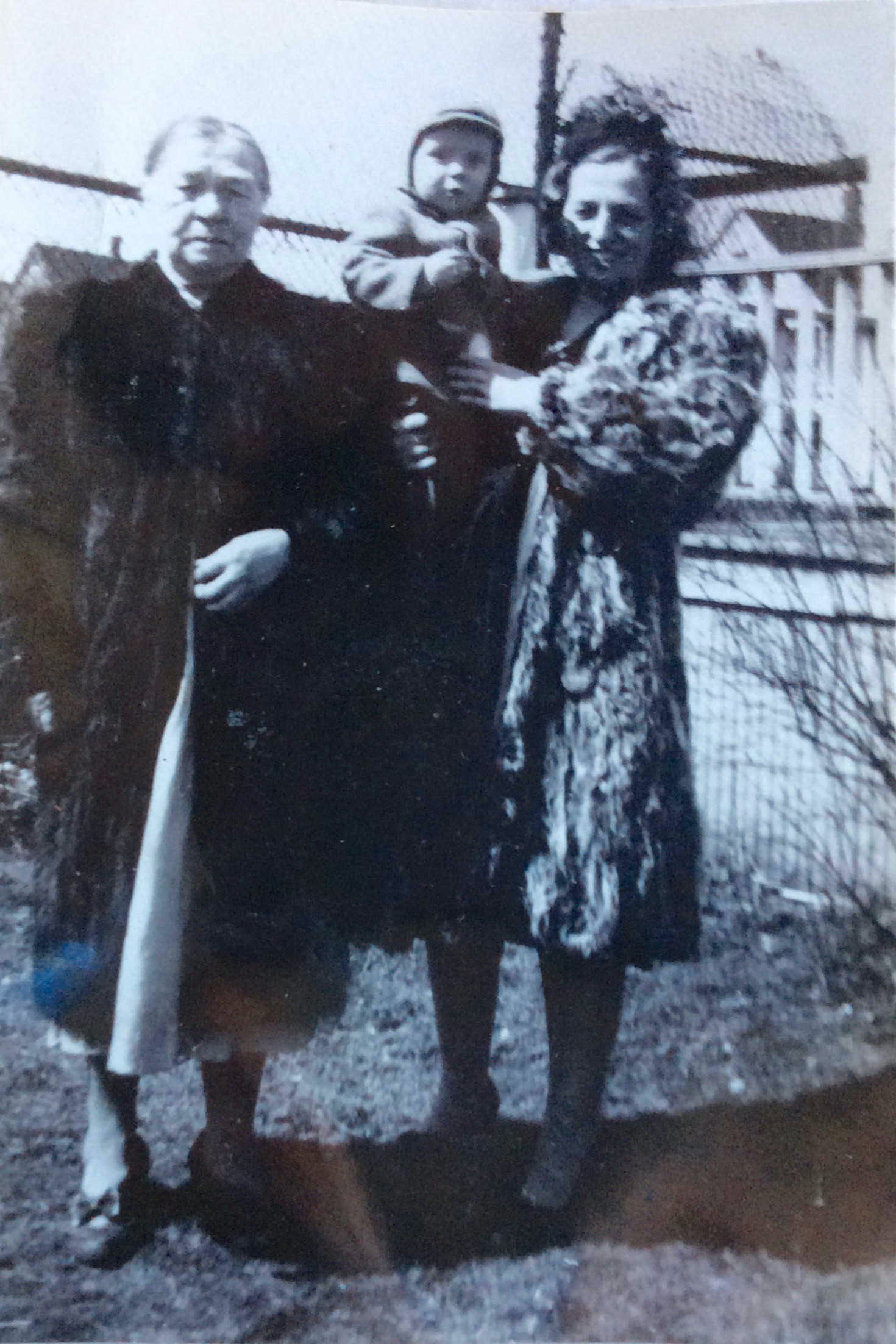 A woman holding a young boy, standing next to an older woman wearing a dark coat