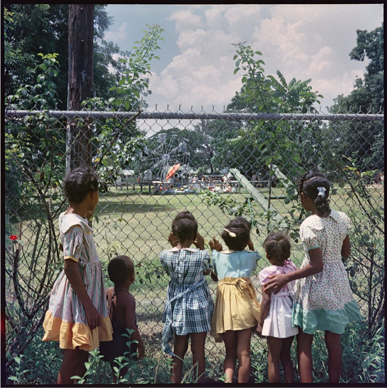 Little black girls in dresses peer through a chainlink fence at a playground.