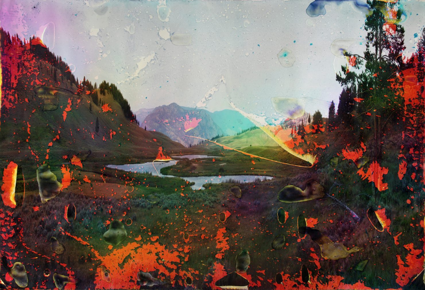 A mountainous lake landscape displays bright, bleeding colors that bubble and streak the addition of lake water to the print.
