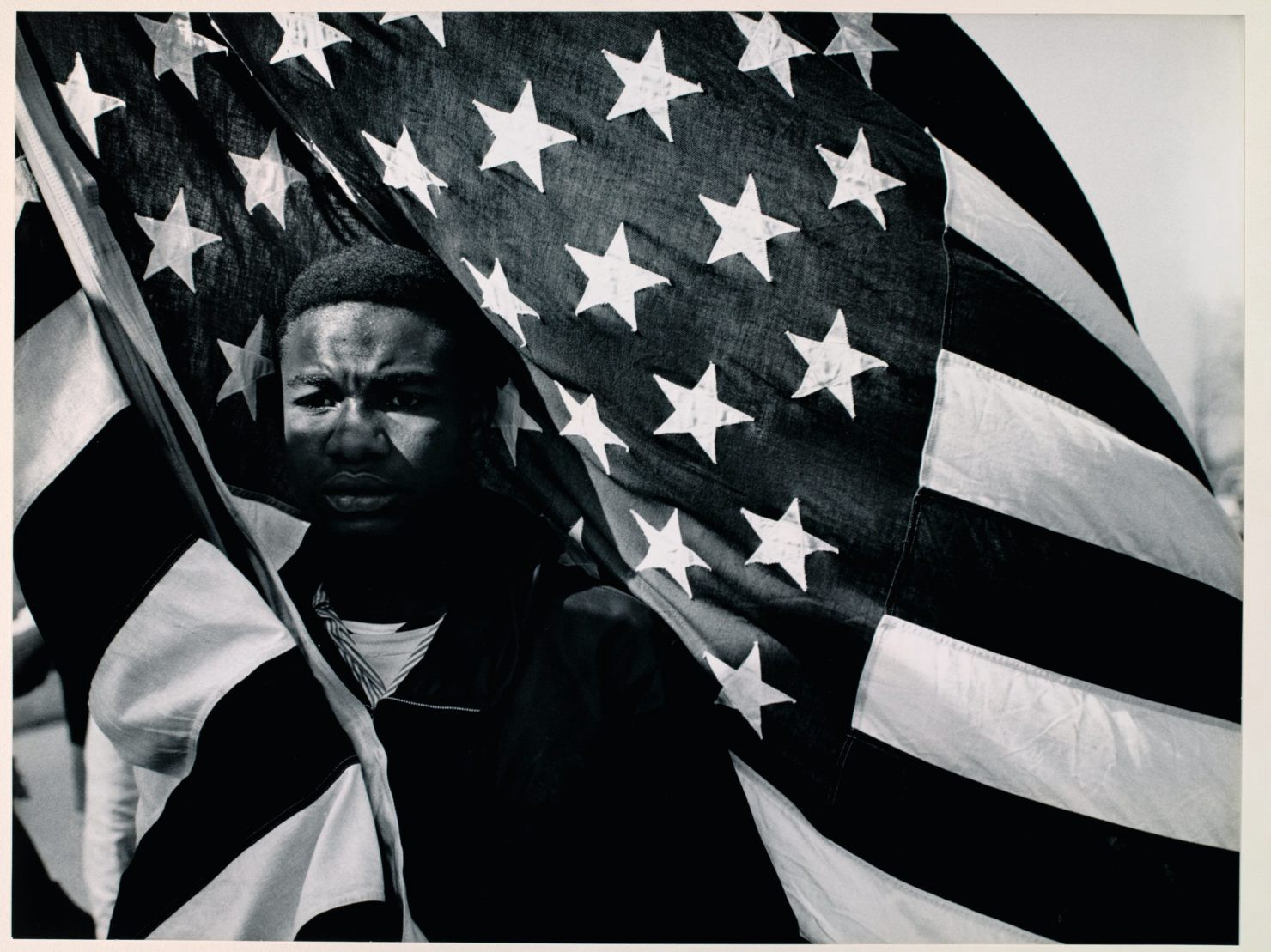 A black teenaged boy stands enwrapped in the American flag, wearing a very emotional expression on his face.