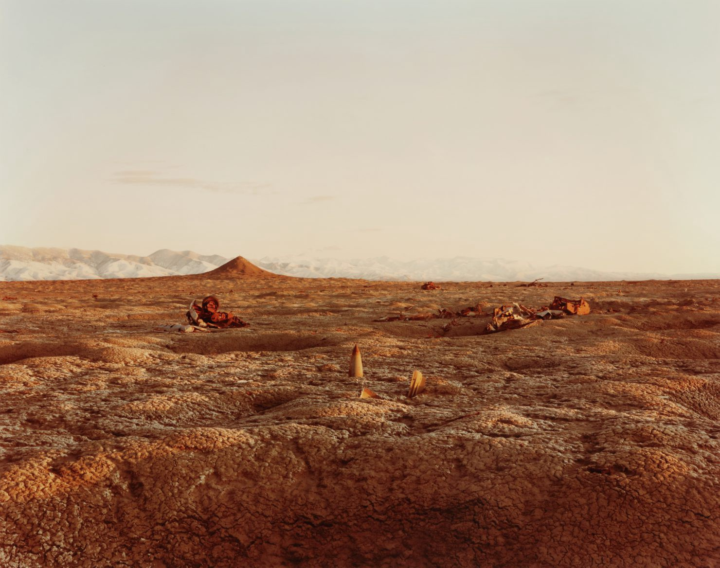 A flat, orange, barren landscape used as a bomb testing area in Nevada is peppered with destroyed vehicle and bomb parts.