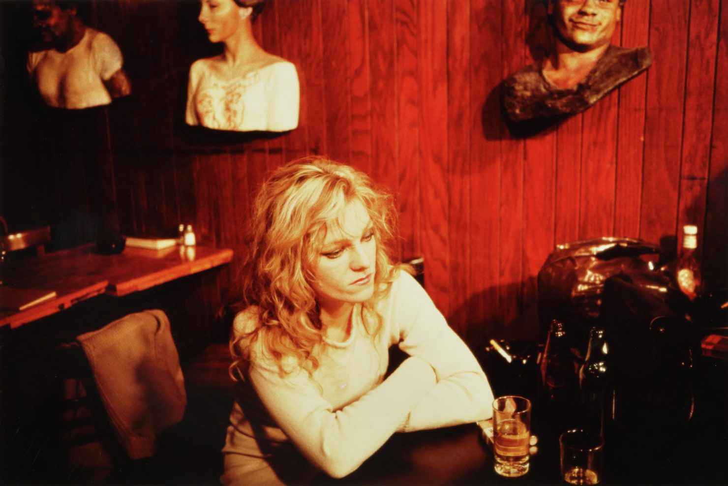 In a reddish wood paneled bar, a blonde woman sits, eyes downcast in thought, arms folded on the bar counter in front of her.